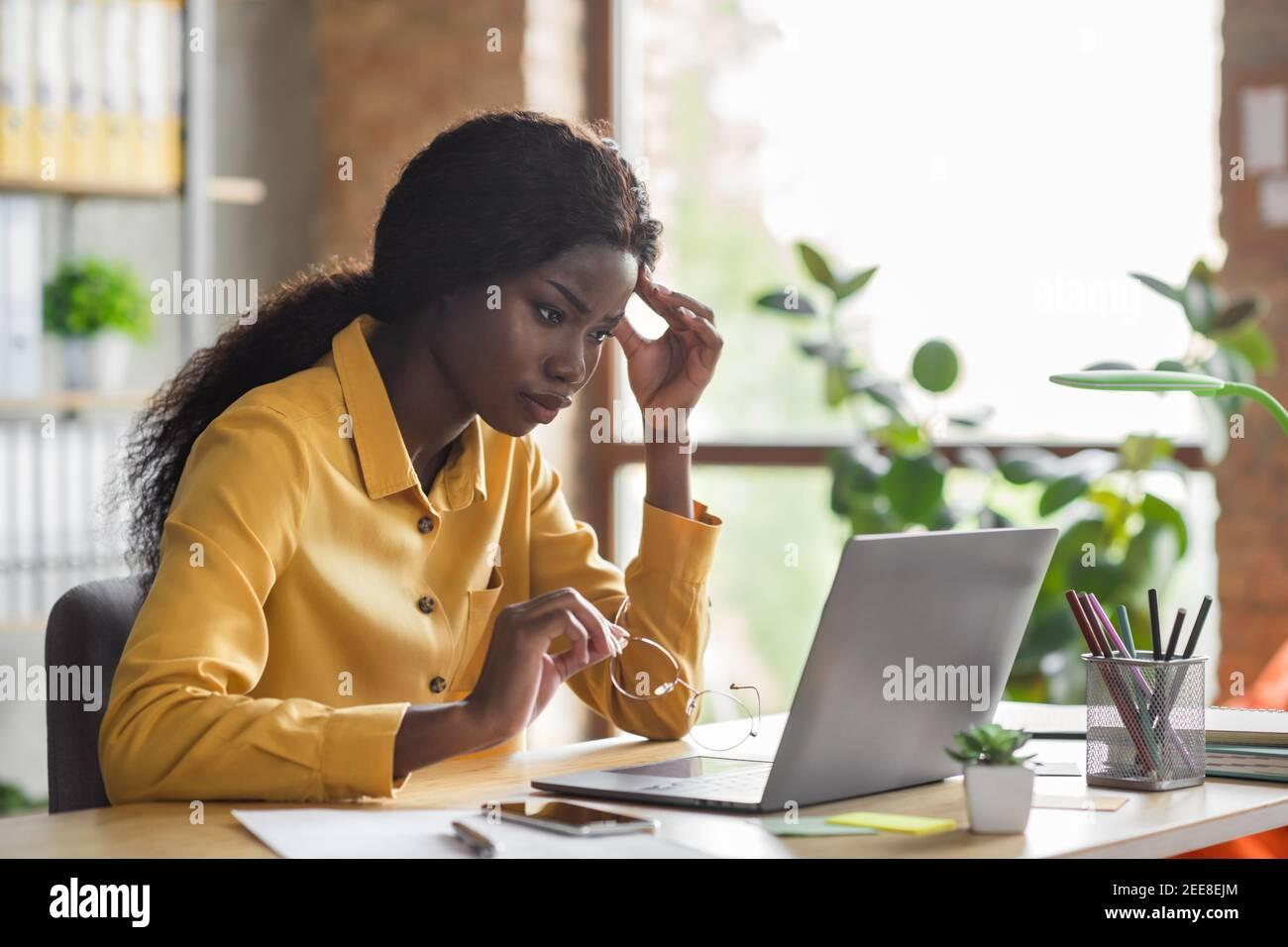 Foto-Porträt von afroamerikanischen Frau berühren Kopf an der Arbeit Laptop im modernen Büro im Innenbereich Stockfoto