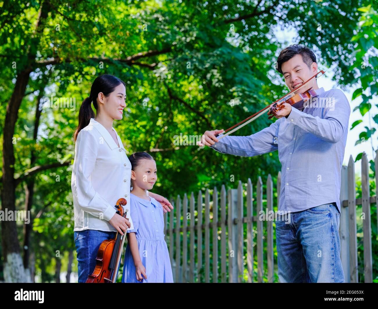 Ein Mann spielt Geige im Park mit Frau und Tochter Stockfoto
