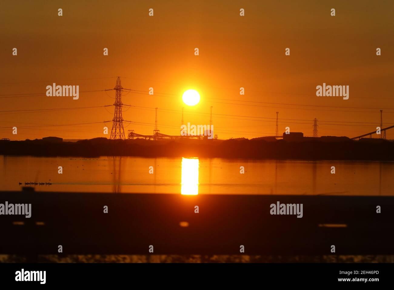 Masten und Stahlwerke Industrie mit der Sonne untergehen in der Hintergrund und leuchtet auf Eglwys Nunydd Reservoir und eine Herde Von Vögeln auf dem Wasser Stockfoto
