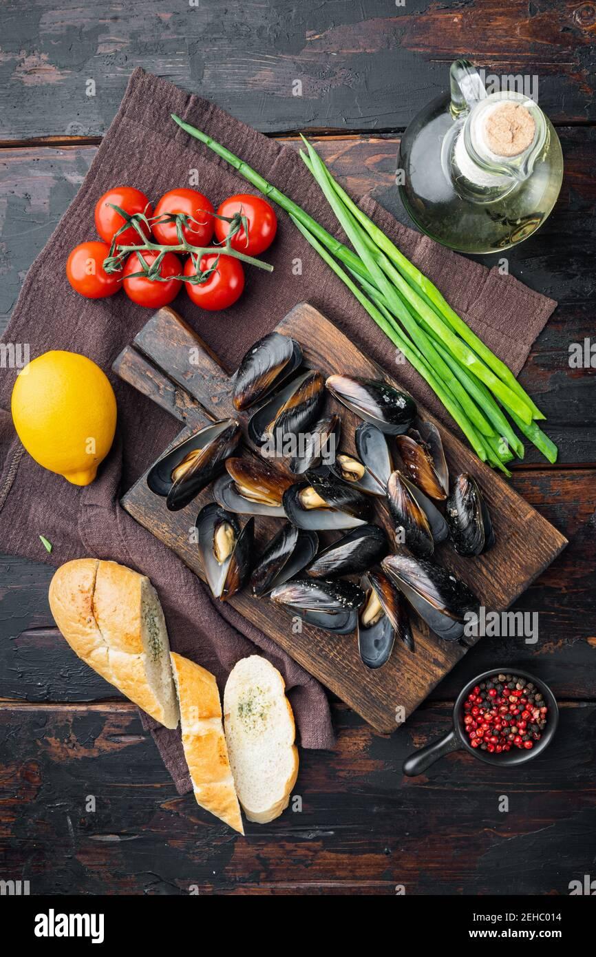 Miesmuscheln-Eintopf in Weißwein und Kräutern, auf Holzschneidebrett, auf altem dunklen Holztischhintergrund, Draufsicht flach liegend Stockfoto
