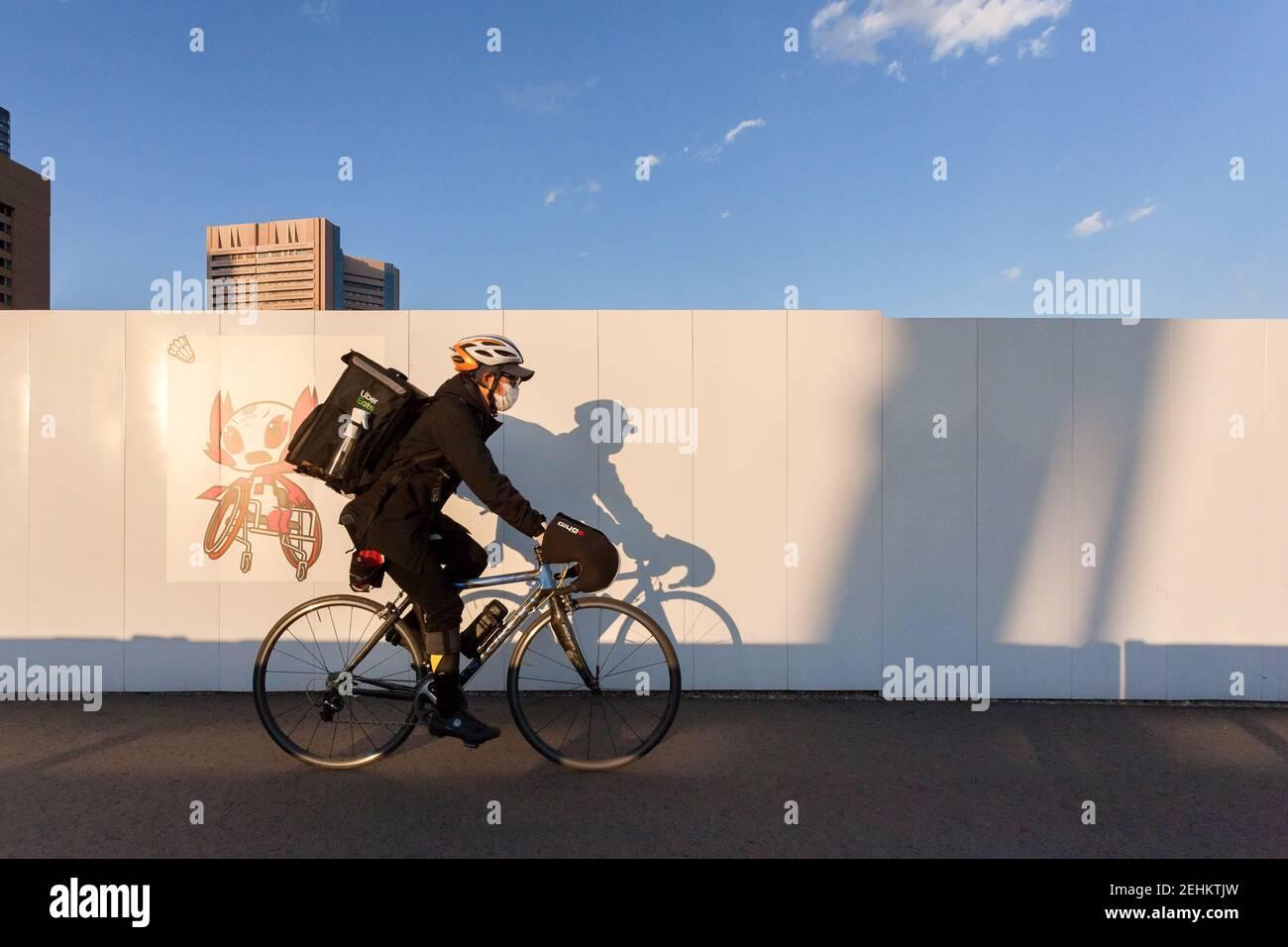Tokio Japan Februar 2021 3rd Ein Uber Isst Zustellmitarbeiter Fahrt An Einem Bildwandplakat Der Olympischen Maskottchen In Tsukiji Vorbei Die Zukunft Der Olympischen Und Paralympischen Spiele 2020 In Tokio Ist Nach Einer Verzogerung