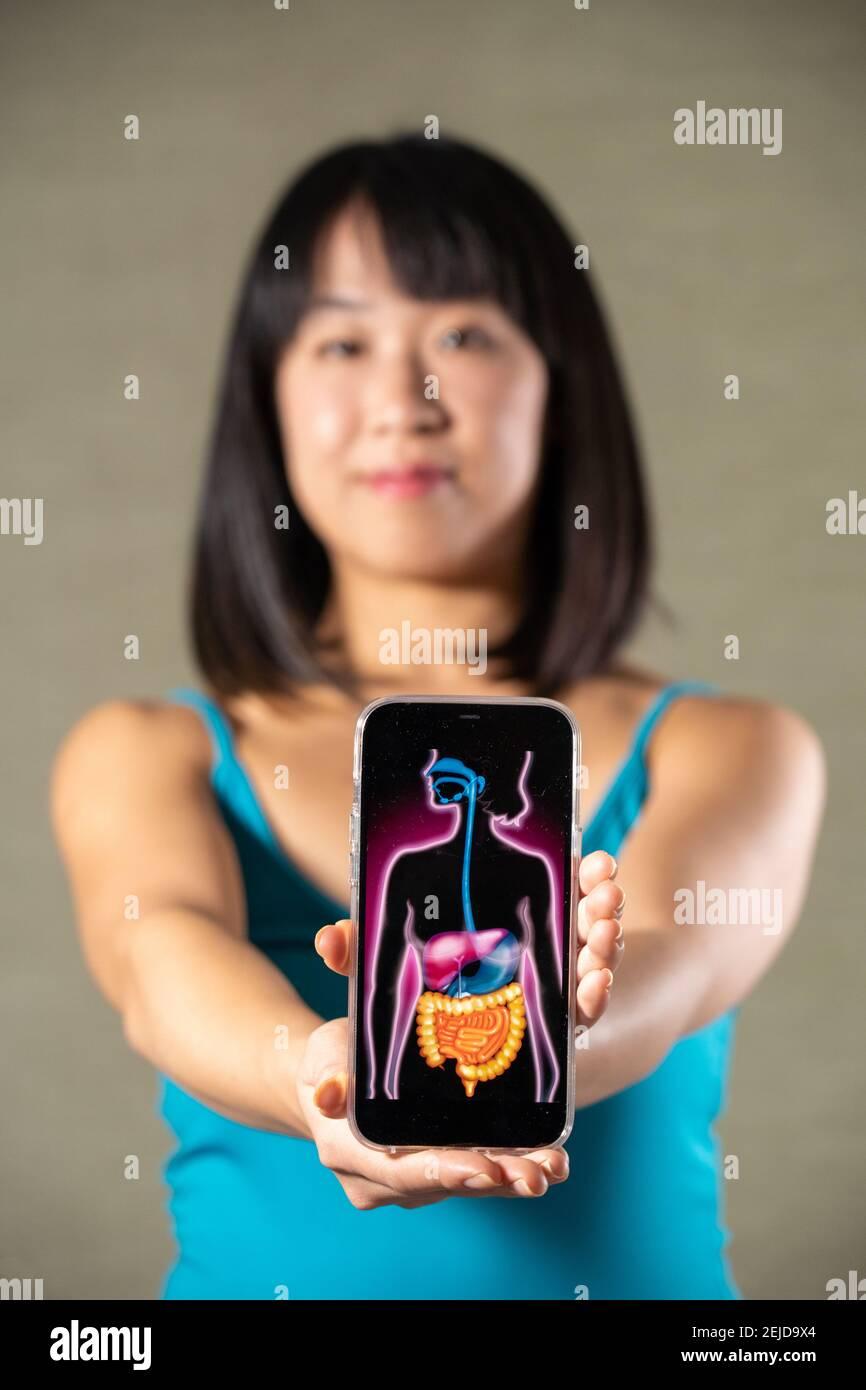 Frau hält Bildschirm mit Zeichnung des Verdauungssystems Stockfoto