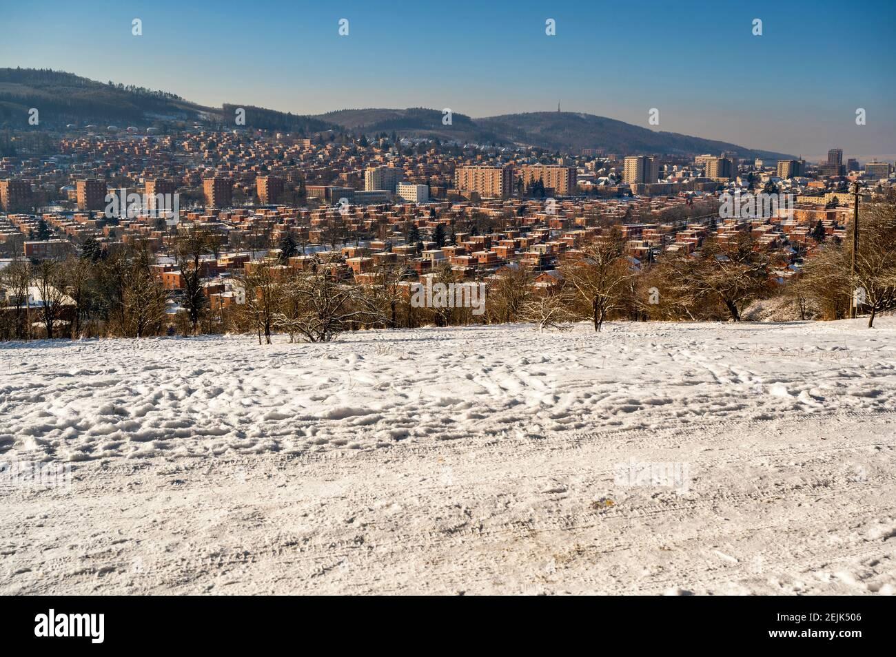 Wohngebiet, einzigartige Architektur von standardisierten roten Backsteinhäusern in der Stadt Zlin, Tschechische republik. Schneebedecktes Stadtpanorama, sonniger Wintertag. Stockfoto