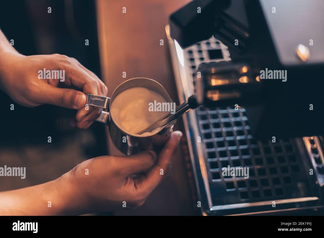Der Barista erwärmt Milchdampf für die Zubereitung von Latten im Café. Stockfoto