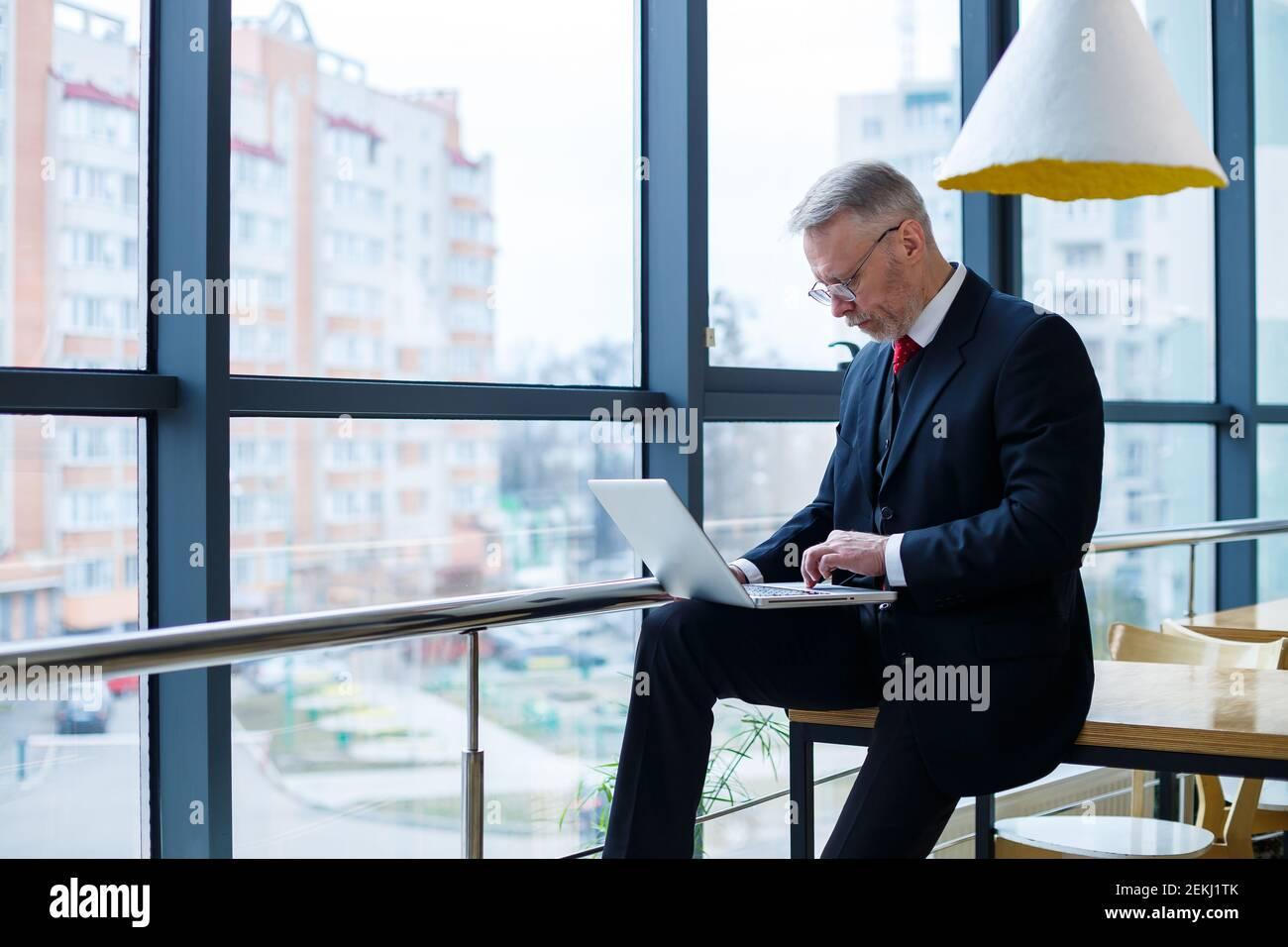 Lächelnder glücklicher Geschäftsführer denkt über seine erfolgreiche berufliche Entwicklung nach, während er mit einem Laptop in seinem Büro in der Nähe eines Gewinns steht Stockfoto