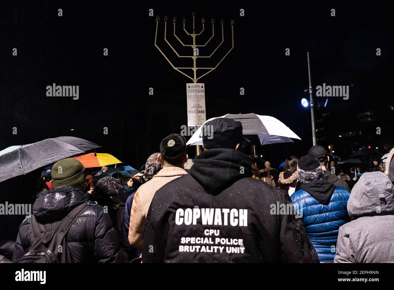 Ein Mitglied von Cop Watch schließt sich den New Yorkern solidarisch an der Beleuchtung der Menorah in der 8th Nacht von Chanukah auf dem Grand Army Plaza in Brooklyn, New York, am 29. Dezember 2019 an. (Foto von Gabriele Holtermann-Gorden/Sipa USA) Stockfoto