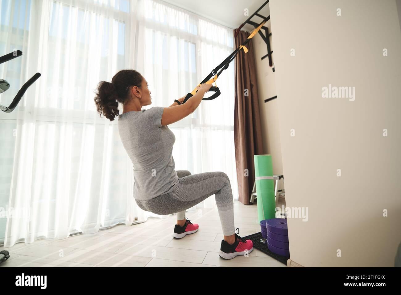 Ein sportliches Mädchen, das zu Hause mit Fitness-Gurten ein Suspension-Training durchführt. Fit Frau Training Beinmuskeln. Konzept der gesunden Lebensweise und Abnehmen wo Stockfoto