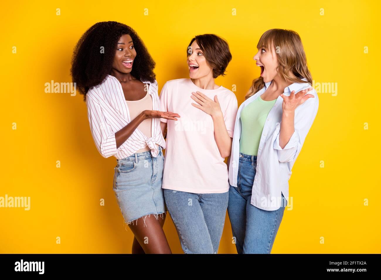 Portrait von drei attraktiven fröhlichen Mädchen reden Spaß Klatschen Umarmung isoliert über hellen gelben Hintergrund Stockfoto