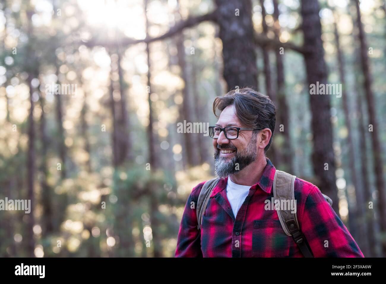 Nahaufnahme eines selbstbewussten bärtigen Mannes in einem Outdoor-Park. Profil jung schön lächelnd bärtiger Mann Junge Erwachsene Hipster Wandern Wald - glücklich peo Stockfoto