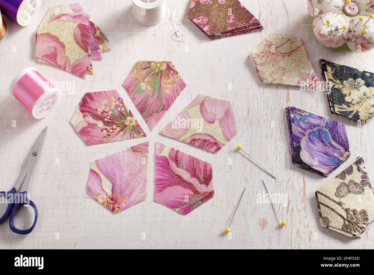 Fünfeckige Stoffstücke, die in Form einer Blume liegen, Stapel von mehrfarbigen Stoffstücken, Nähzubehör auf einer weißen Oberfläche Stockfoto