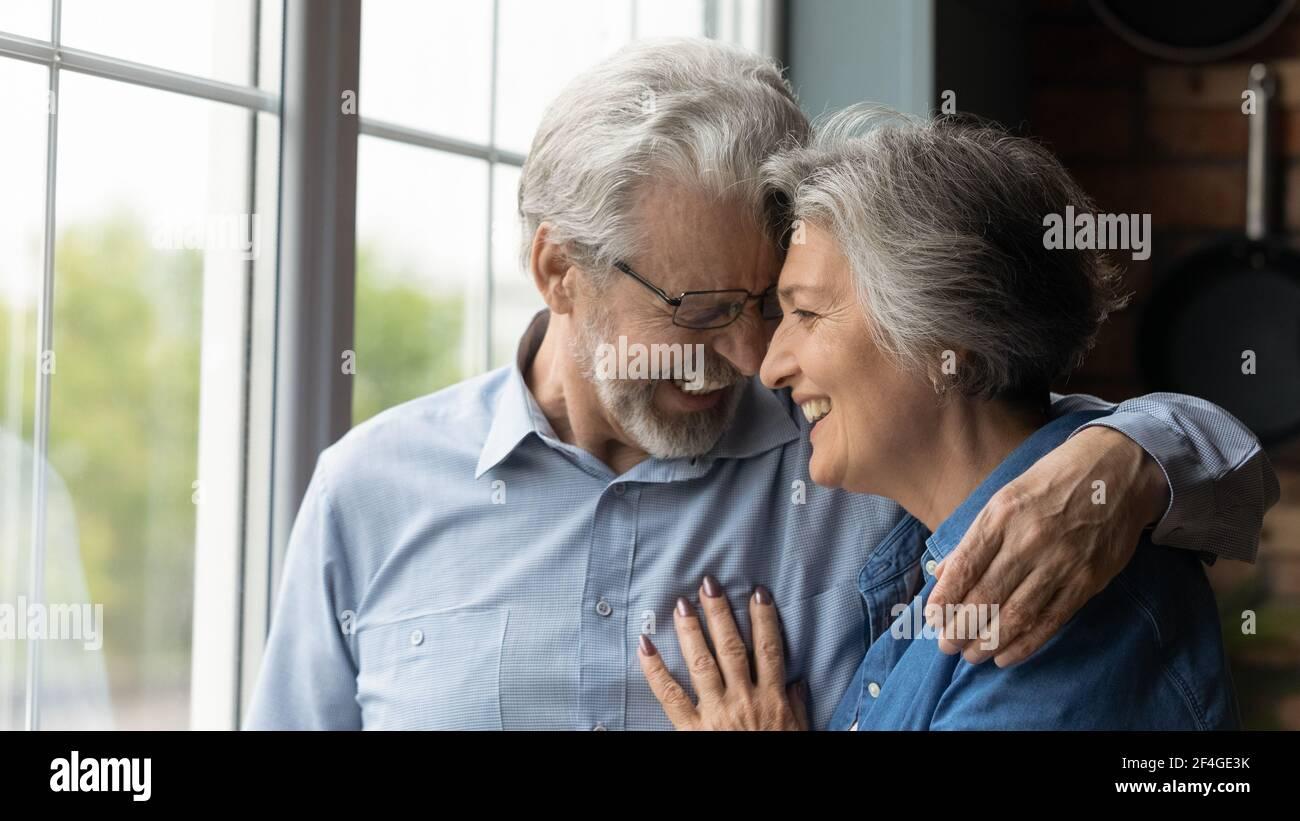 Liebevolle liebevolle Rentnerpaar haben Datum lachen kuscheln berühren Stirn Stockfoto