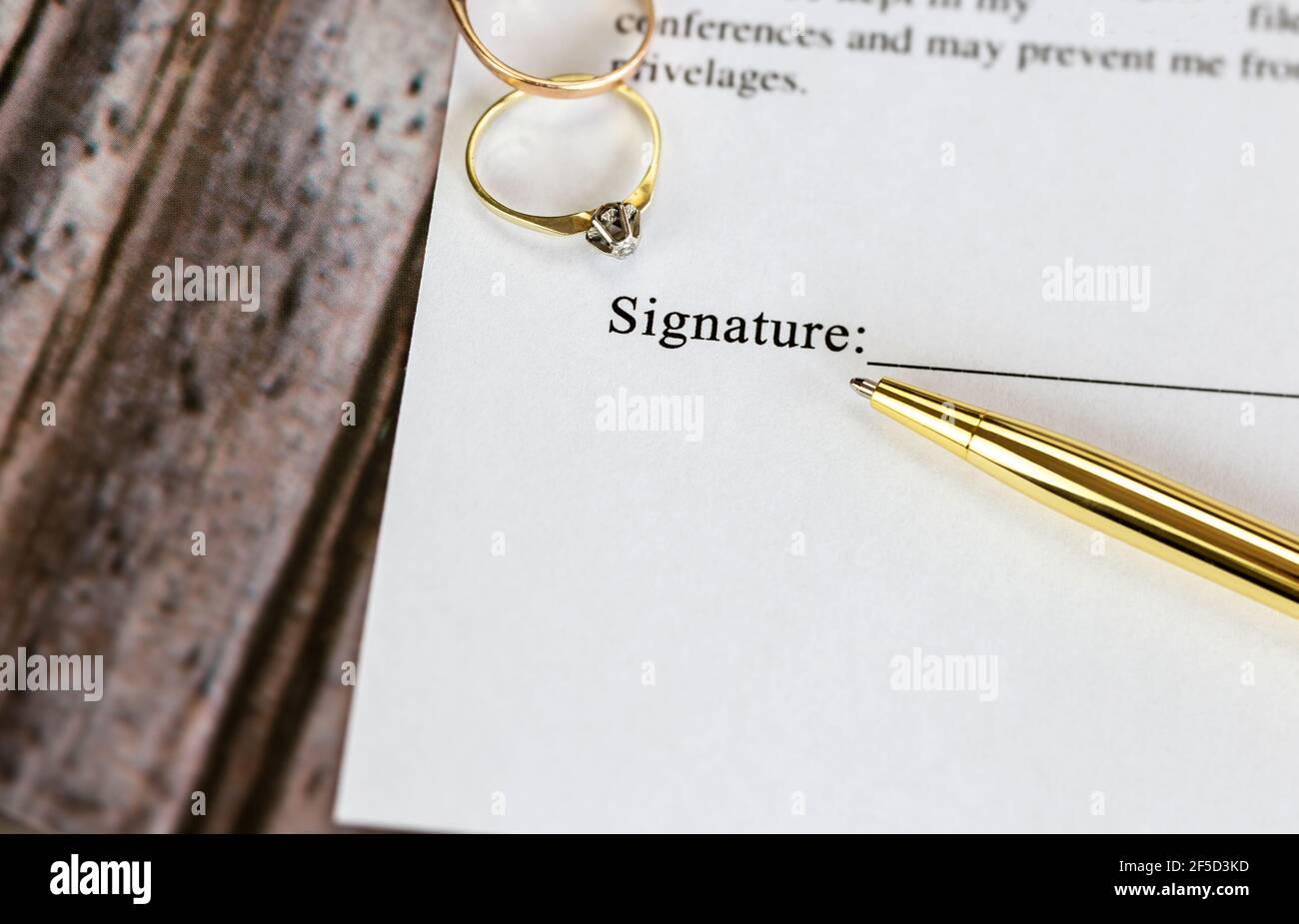 Heiratsvertrag mit zwei goldenen Eheringen und Goldstift, prenuptial Vereinbarung, Makro Nahaufnahme, unterzeichnen mit signanture, Dokument, Vereinbarung Konzept Stockfoto
