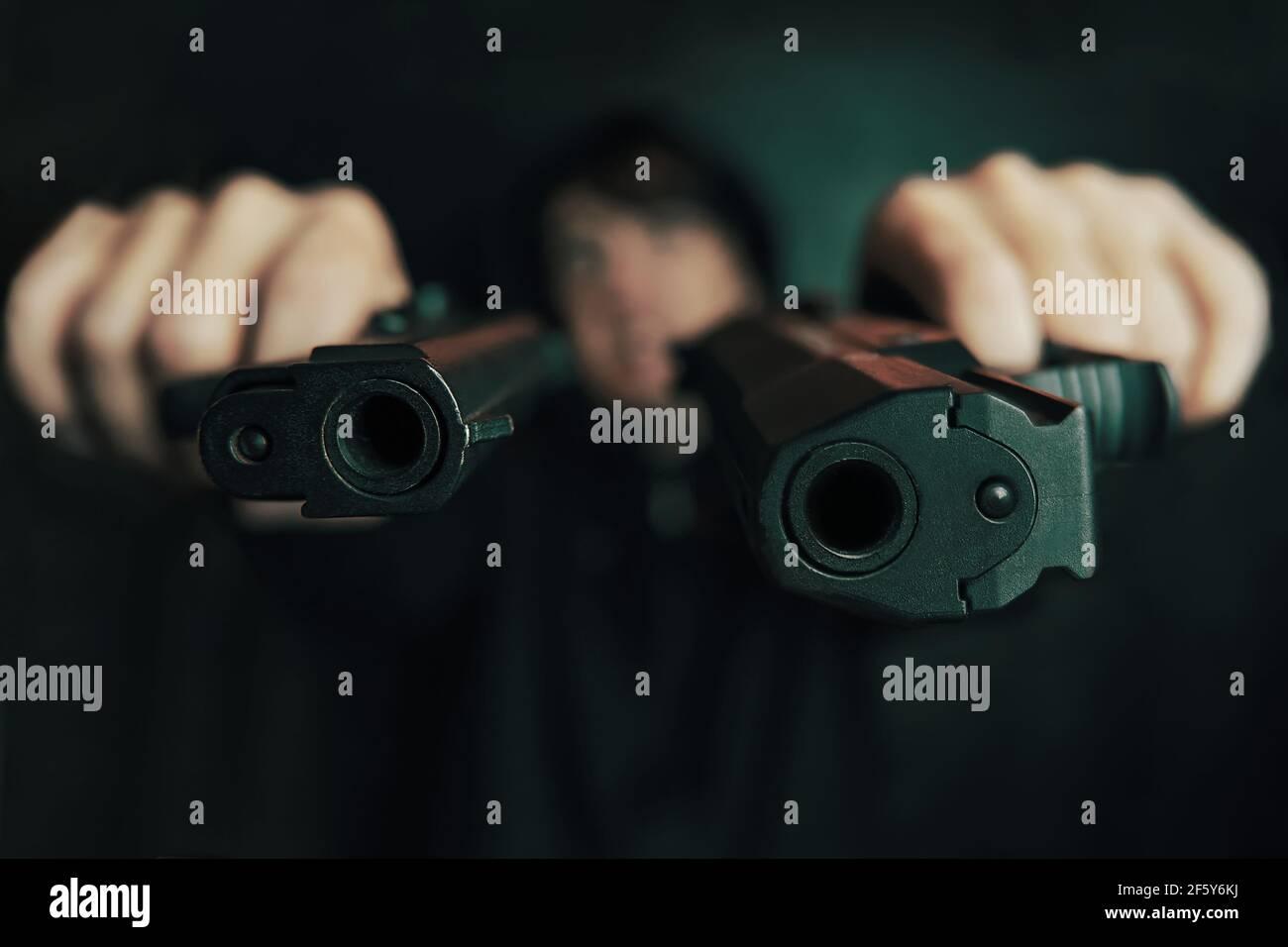 Nahaufnahme von zwei Geschützmuzzles. Guy droht mit Schusswaffe. Zwei Pistolen in Menschenhand sind auf die Kamera gerichtet. Verbrecher mit Waffe. Stockfoto