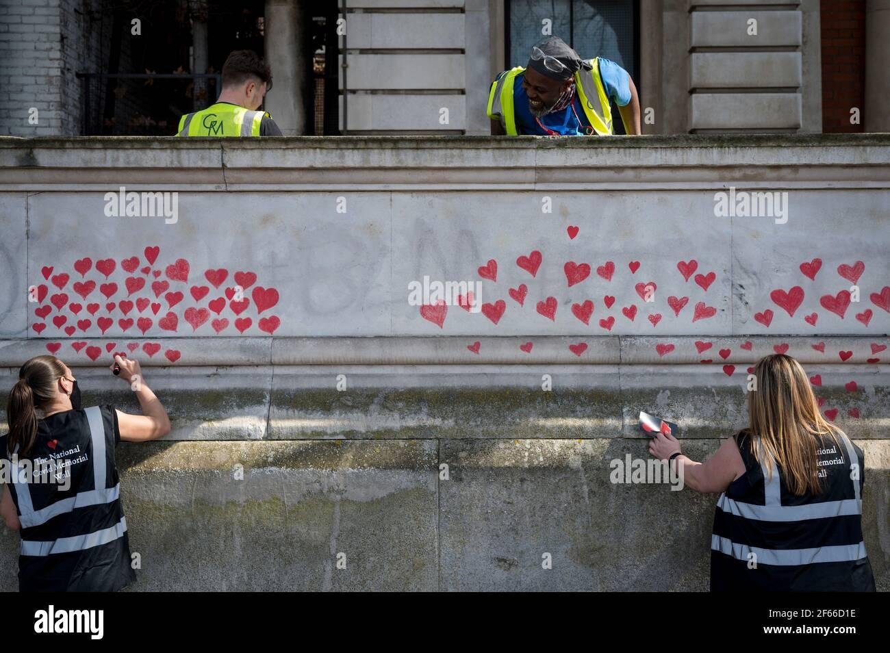 London, Großbritannien. März 2021, 30th. Freiwillige ziehen Herzen an eine Wand in Lambeth an der Themse, wobei jedes Herz jemanden repräsentiert, der während der laufenden Coronavirus-Pandemie in Großbritannien gestorben ist. Sie wurde von den Covid-19 Hinterbliebene Familien für Gerechtigkeit geschaffen und wird sich bis zur Fertigstellung für eine halbe Meile erstrecken. Kredit: Stephen Chung/Alamy Live Nachrichten Stockfoto