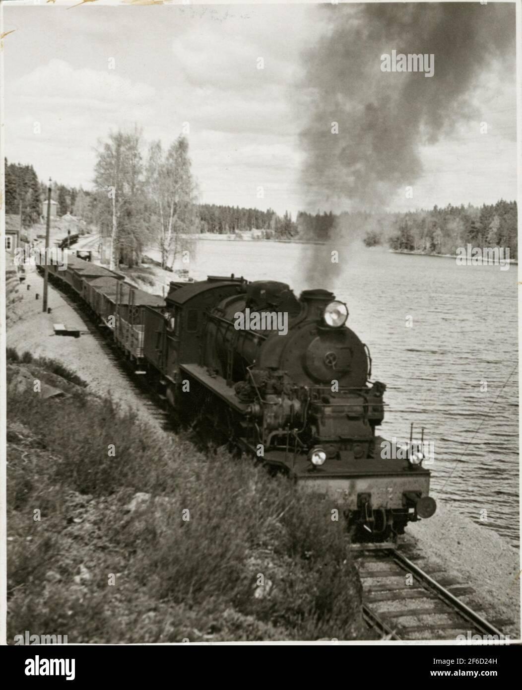 Die Verkehrsgesellschaft Grängesberg - Oxelösund Eisenbahn, TGOJ M3T 73 vor einer Reihe von Erzautos in Harsjön. Stockfoto