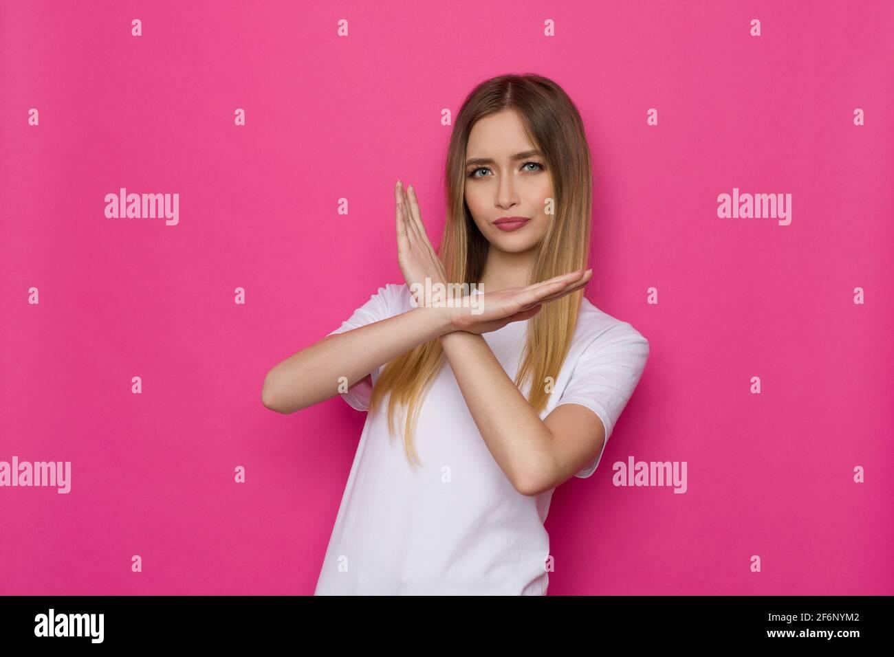 Selbstbewusste junge Frau zeigt KEIN Zeichen mit gekreuzten Händen. Studio-Aufnahme in der Taille auf rosa Hintergrund. Stockfoto