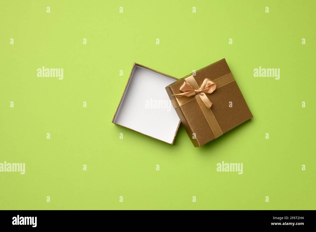 Leere quadratische goldene Schachtel mit Pappschleife auf grünem Hintergrund, Geschenk offen, Draufsicht. Stockfoto