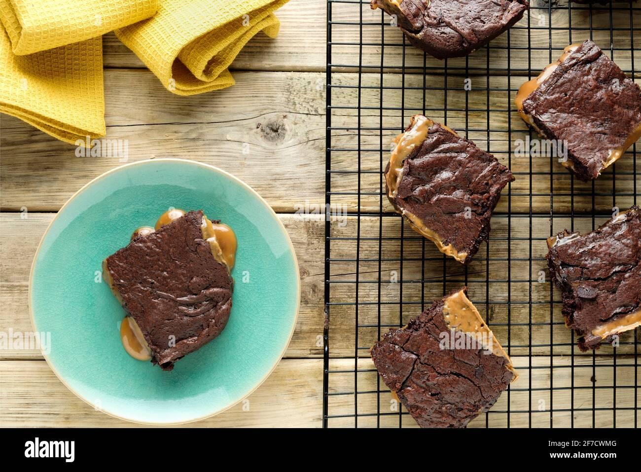 Eine frisch gekochte Charge gesalzener Karamell-Brownies, die auf einem Drahtgestell abkühlen. Ein Brownie ist überzogen und sickelt geschmolzenes Karamell auf den Teller Stockfoto