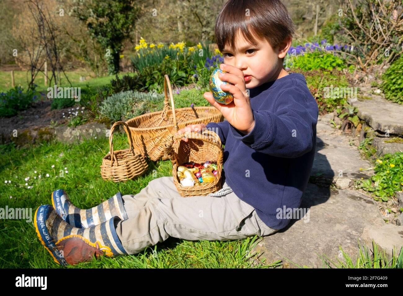 Kleiner Junge, der nach der Ostereiersuche im Garten sitzt Mit Korb mit Ostereiern, die großes Schokoladenei zeigen In seiner Hand Wales UK KATHY DEWITT Stockfoto