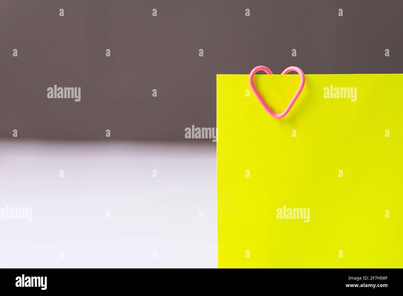 Büroklammern in Herzform auf fluoreszierenden Haftnotizen auf weißem Hintergrund. Stockfoto