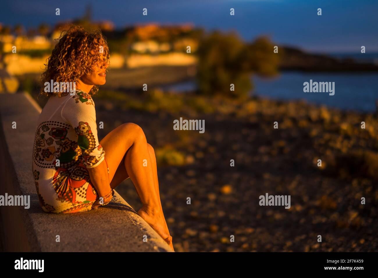 Eine Frau setzt sich draußen hin und genießt das Sonnenuntergang-Licht Vor ihr - Strand und Meer im Hintergrund - Tourismus und Sommerurlaub Reisen Stockfoto