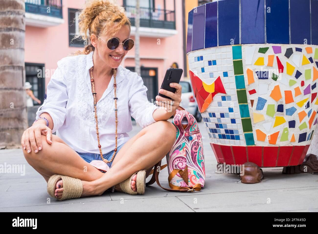 Fröhliche junge Touristenfrau wit auf dem Boden in der Stadt und verwenden Sie Wireless WiFi-Verbindung kostenlos imit Telefon tun Eine Videokonferenz zu Frie Stockfoto