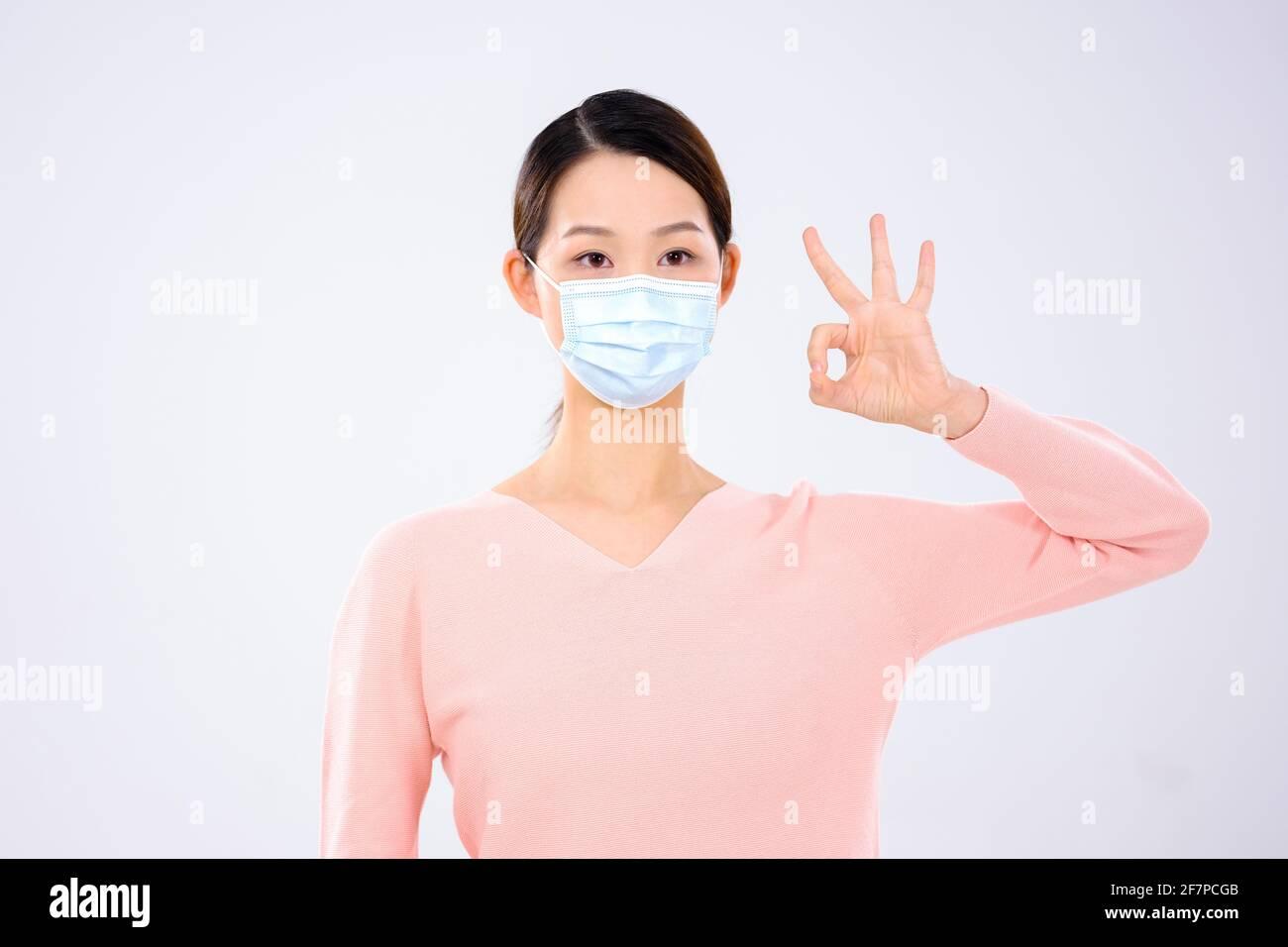 Eine junge Frau, die eine Maske trägt, machte ein Zeichen dafür Zustimmung Vorderansicht Stockfoto