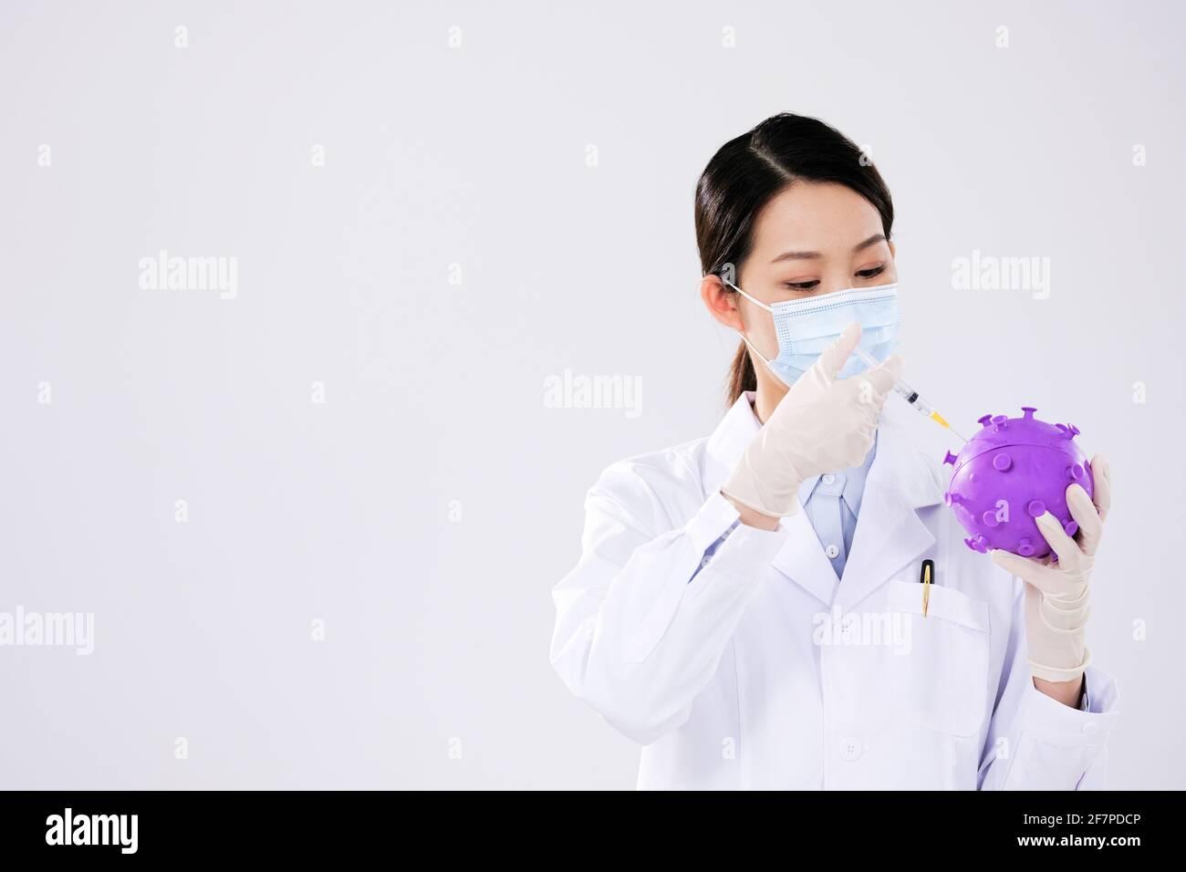 Eine Ärztin injiziert Virusmodelle Stockfoto