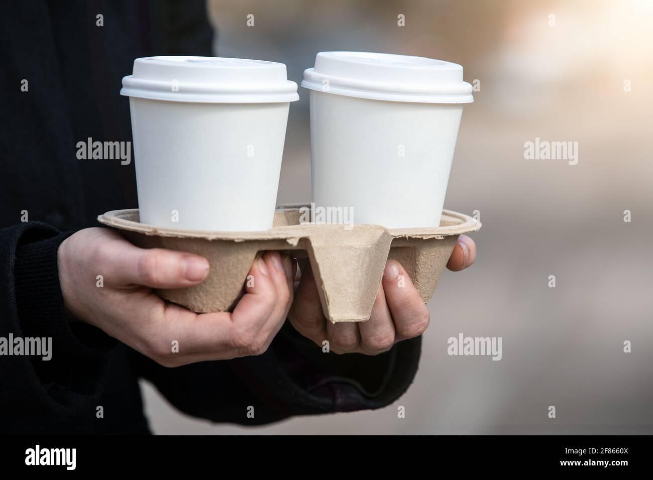 Pappbecher zum Mitnehmen. Am frühen Morgen, Frühstück und Beginn des Arbeitstages. Stockfoto