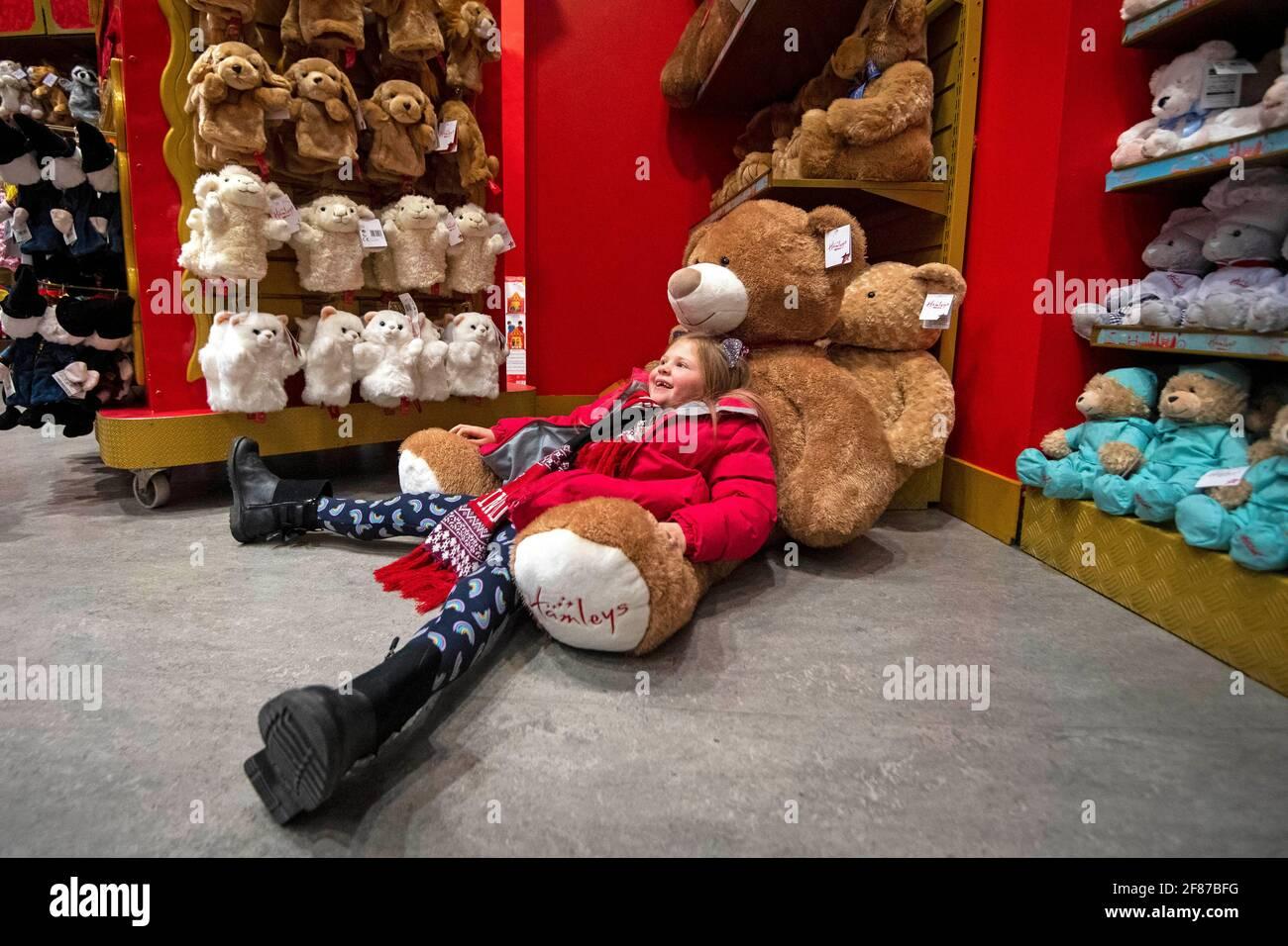 Lyla Stevens-Pierce, 7 Jahre alt, sitzt während der Wiedereröffnung des Spielzeugladens Hamleys in der Regent Street, London, auf einem riesigen Teddybären, während England mit der weiteren Lockerung der Sperrbeschränkungen einen weiteren Schritt zurück in Richtung Normalität unternimmt. Bilddatum: Montag, 12. April 2021. Stockfoto