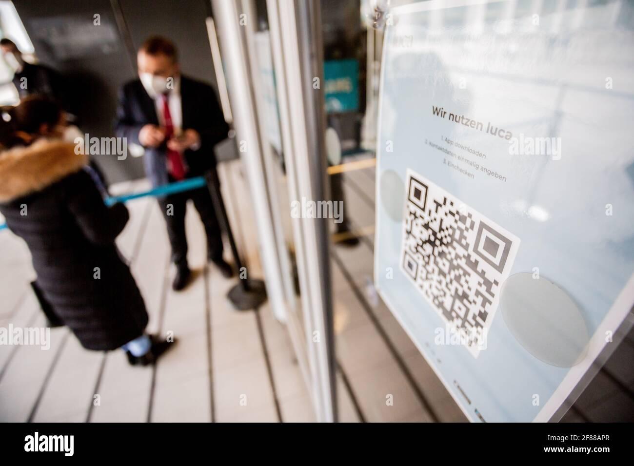 Berlin, Deutschland. April 2021. Ein QR-Code zum Herunterladen der Luca App hängt am Eingang eines Bekleidungshauses am Alexanderplatz. Die App dient zur Bereitstellung von Daten für eine mögliche Kontaktverfolgung. Quelle: Christoph Soeder/dpa/Alamy Live News Stockfoto