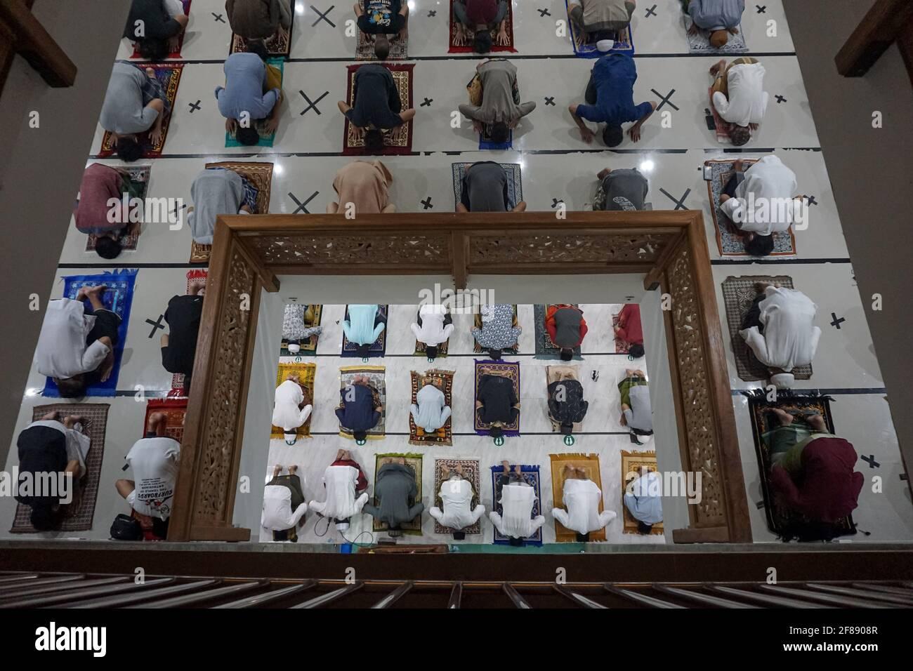 Badung, Bali, Indonesien. April 2021. Die Menschen setzen distanzierte Linien aufgrund des Covid-19 Gesundheitsprotokolls während der Gebete. Indonesische Muslime von Bali beginnen die ersten Tarawih-Massengebete in der Al-Hasanah-Moschee, Canggu, da die Regierung feststellte, dass das erste Datum des islamischen Monats Ramadan auf den 12. April 2021 fällt. Morgen, dem 13. April 2021, werden Muslime im folgenden Monat mit dem Fasten beginnen. (Bild: © Dicky BisinglasiZUMA Wire) Stockfoto