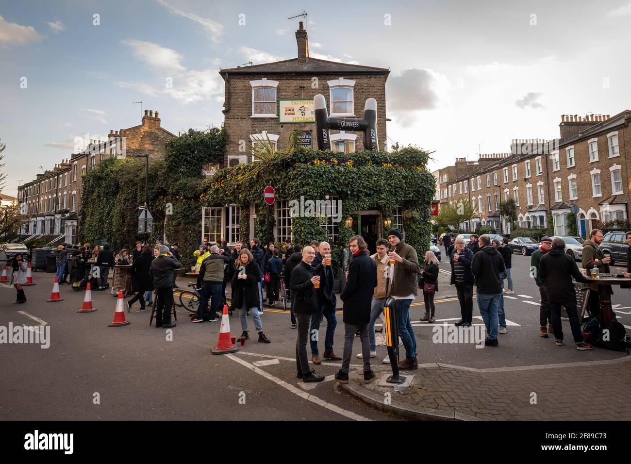 London, Großbritannien. 12. April 2021. Trinker vor dem stoppenden Fullback Pub im Finsbury Park, North London, das heute wieder für das Trinken von draußen geöffnet wurde, da die Lockdown-Maßnahmen in ganz Großbritannien gelockert werden. Bilddatum: Montag, 12. April 2021. Bildnachweis sollte lauten: Matt Crossick/Empics/Alamy Live News Stockfoto