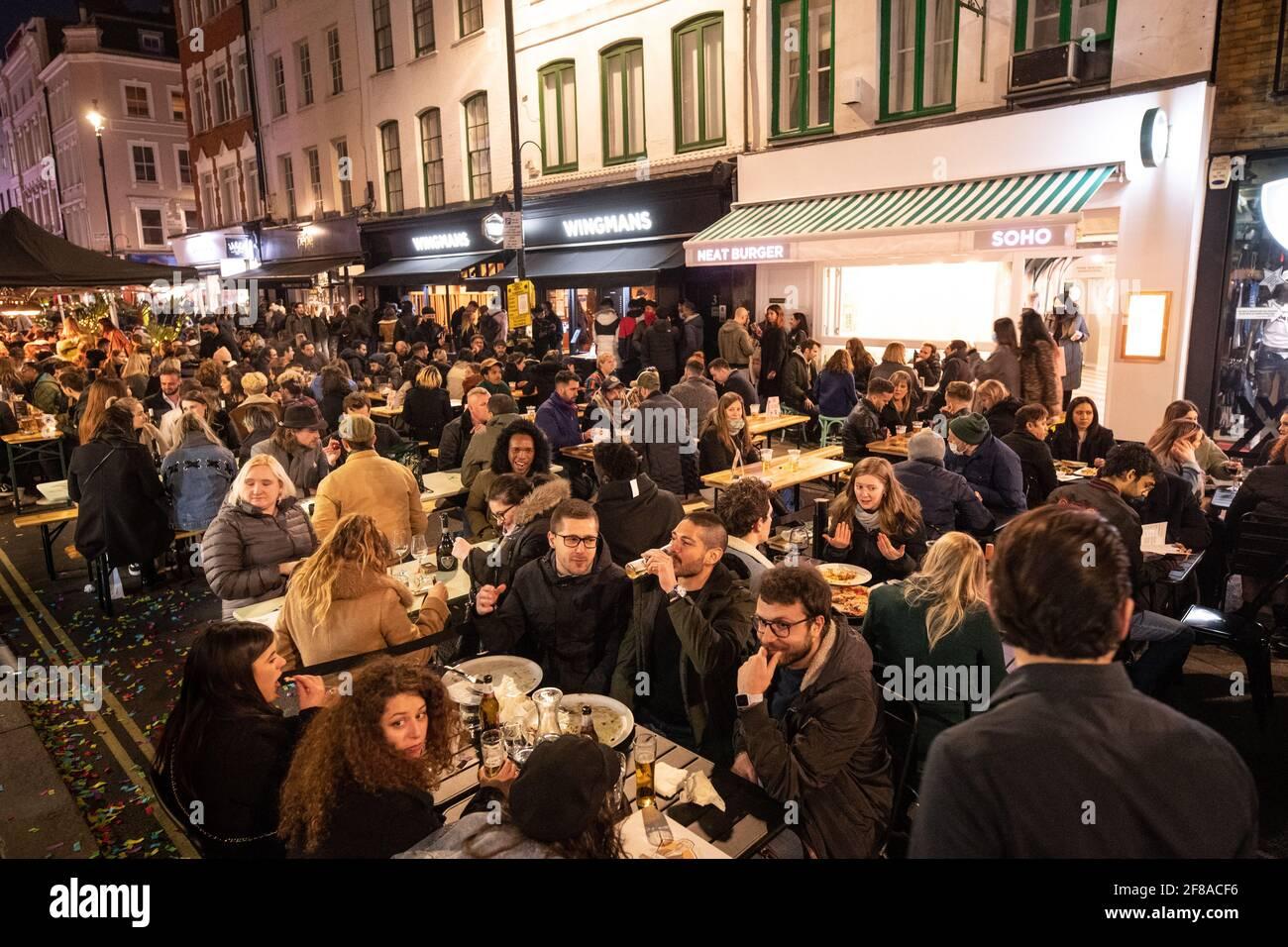 London, Großbritannien. 13. April 2021. Menschen versammeln sich in Soho, London, wo Straßen für den Verkehr gesperrt wurden, als Bars und Restaurants für Essen und Trinken im Freien geöffnet wurden, da die Sperrmaßnahmen in ganz Großbritannien gelockert werden. Bilddatum: Dienstag, 13. April 2021. Bildnachweis sollte lauten: Matt Crossick/Empics/Alamy Live News Stockfoto