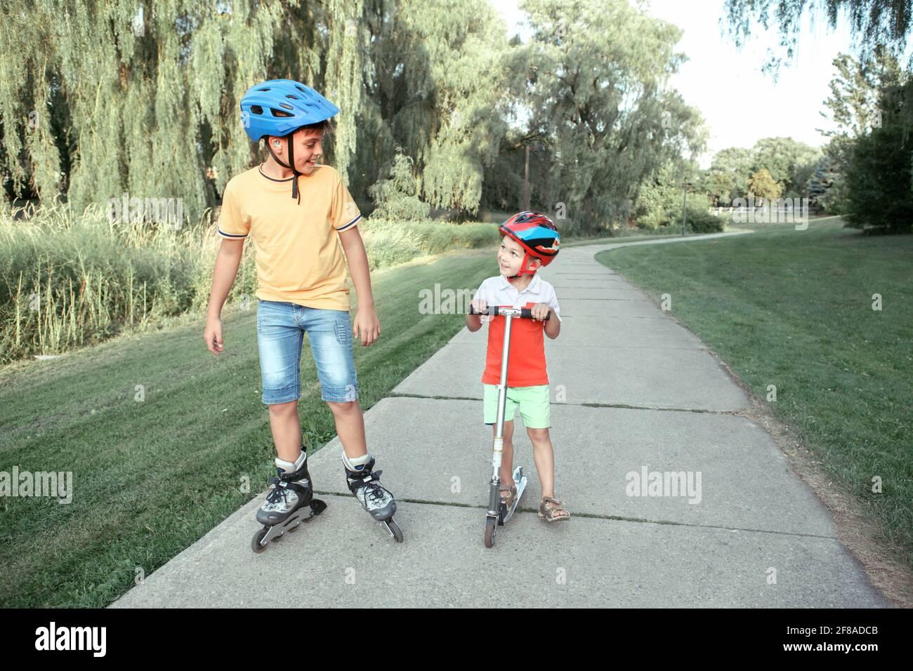 Kaukasische Jungen Brüder in Helmen Reiten Rollschuhe und Roller auf der Straße im Park. Saisonale Outdoor-Aktivitäten für Kinder Sport. Gesundes Kindheitsleben Stockfoto