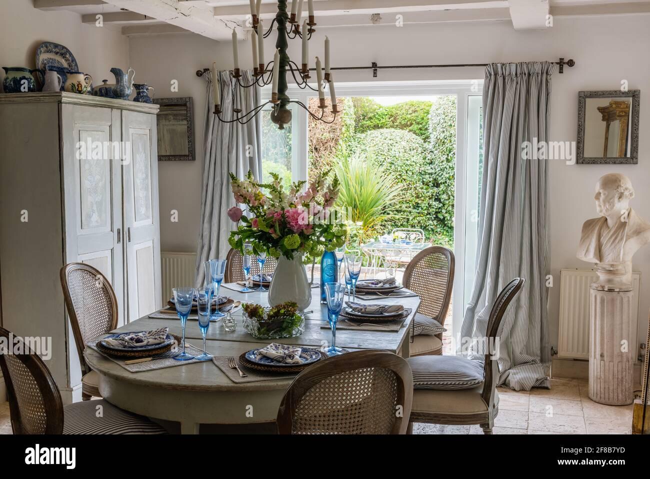 Glaswaren auf dem Esstisch mit Blick auf den Garten bei der Renovierung der West Sussex-Küste aus den 1930er Jahren. Stockfoto