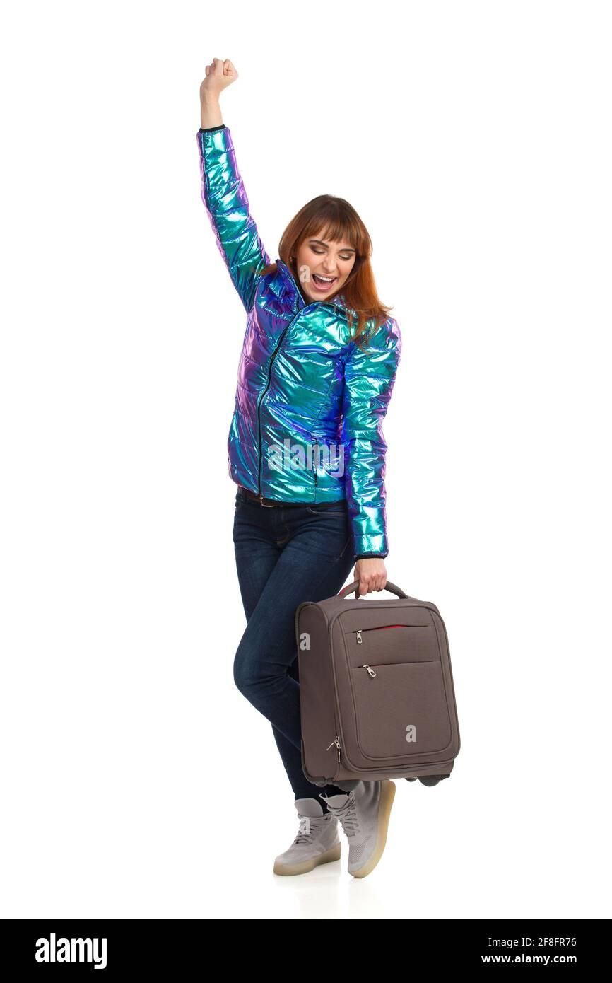Junge Frau mit Koffer hält die Faust angehoben und schreit. Studioaufnahme in voller Länge, isoliert auf Weiß. Stockfoto