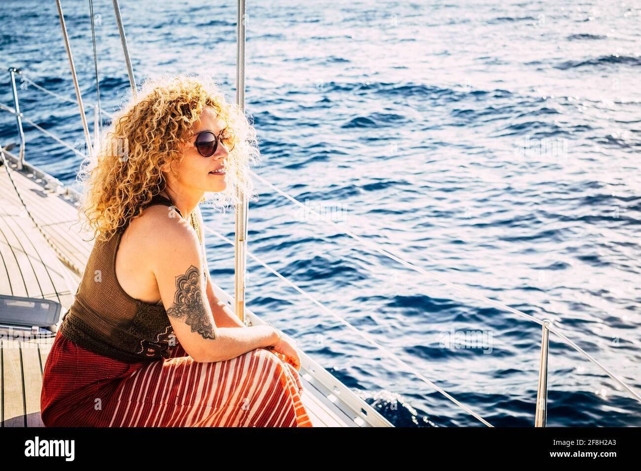 Fröhliche attraktive junge Erwachsene blonde Frau lächeln und genießen Sie die Ausflug auf dem Segelbootdeck mit Blick auf die Blaues Meer um - Konzept von Stockfoto