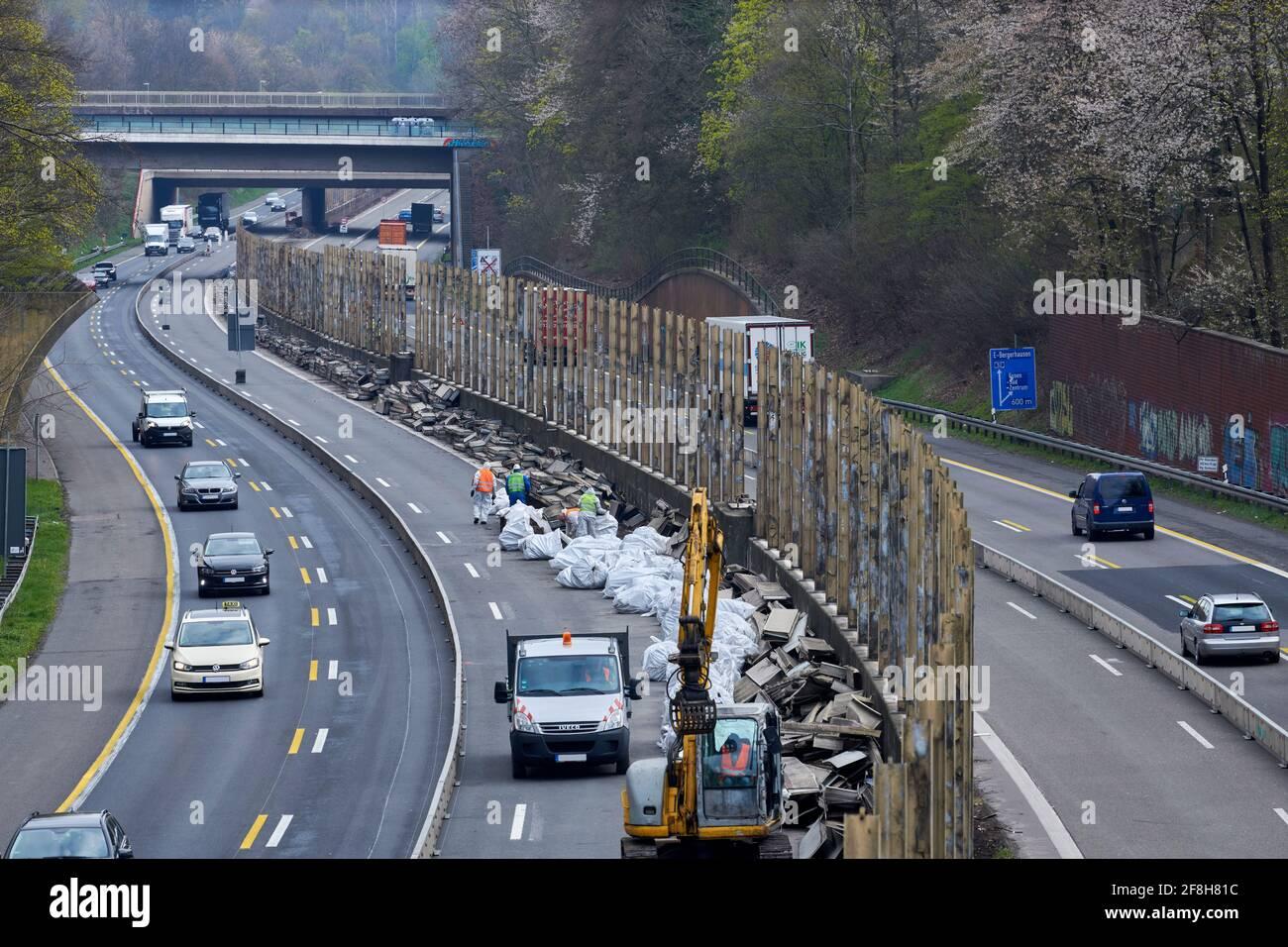 Sanierung Laermschutzwand auf der A52. Mehrere Arbeiter in Schutzangriffen und Atemmaske frachten den Inhalt von Schallschutzelementen in weisse SAE Stockfoto