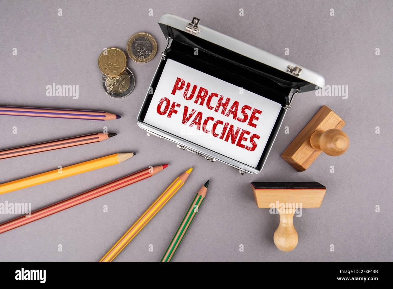 Kauf von Impfstoffen. Visitenkarten, Buntstifte und Euro-Geld auf einem grauen Schreibtisch. Stockfoto