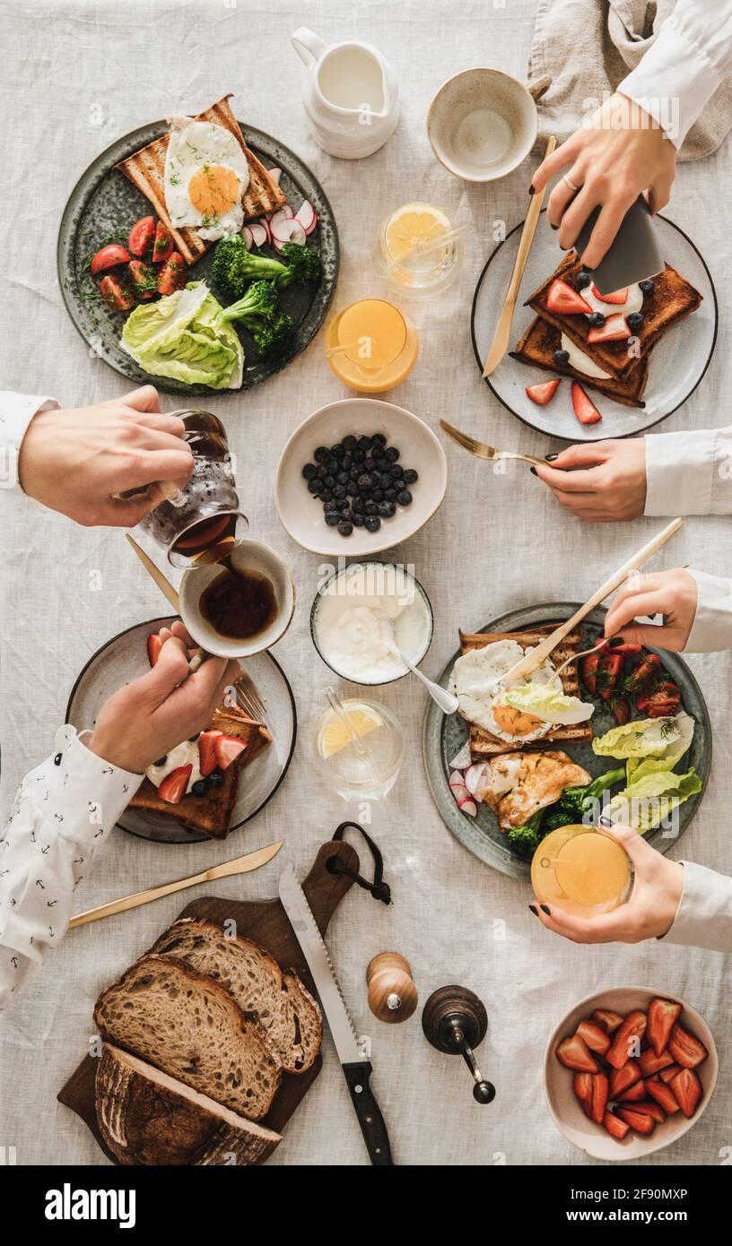 Familie, die zusammen frühstücken oder zu Abend essen. Flacher Tisch mit französischem Toast, Spiegelei, frischem Brot, Gemüse, Beeren und Menschenhänden Stockfoto