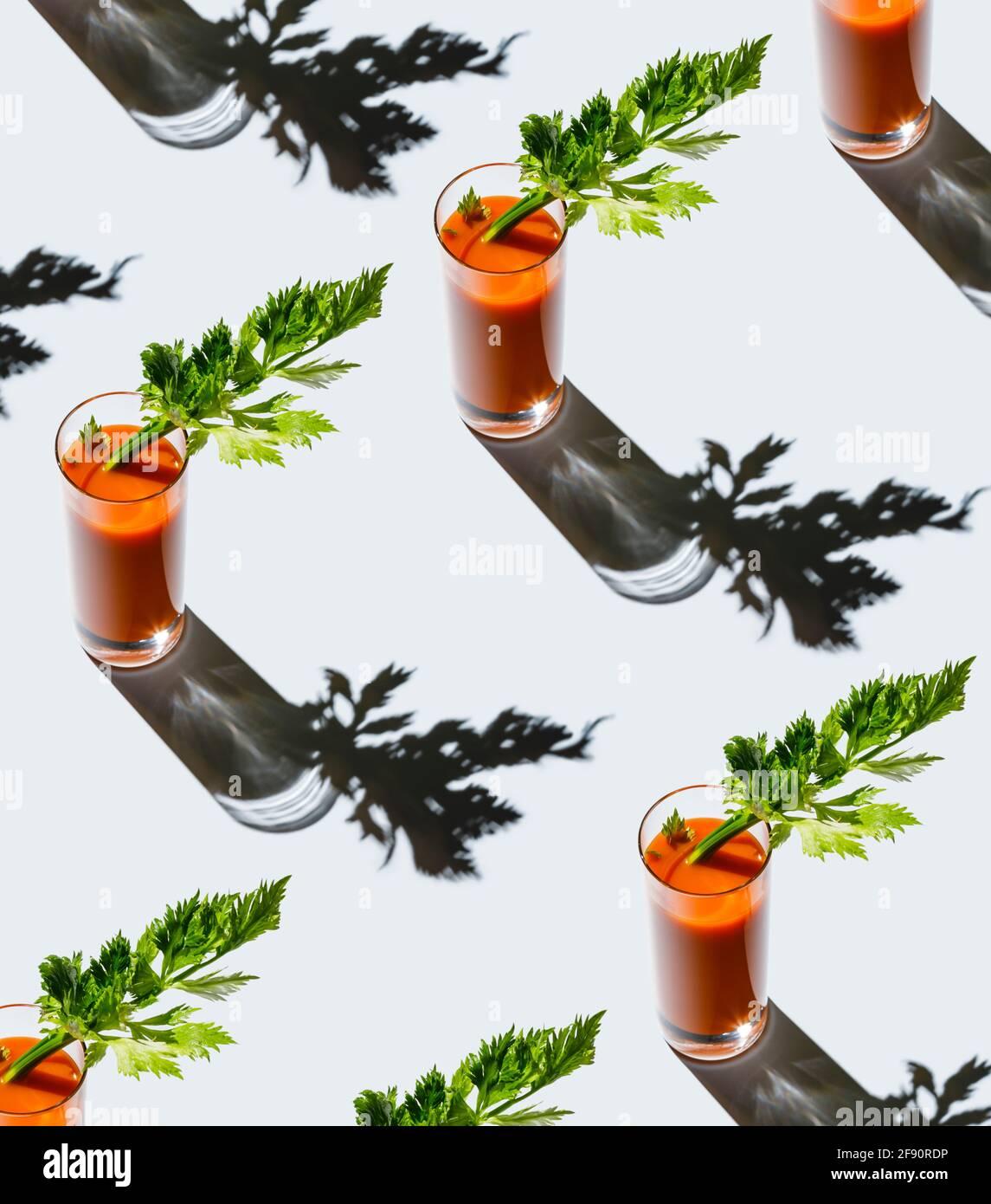 Karottensaft mit Sellerie auf grauem Hintergrund Muster Stockfoto