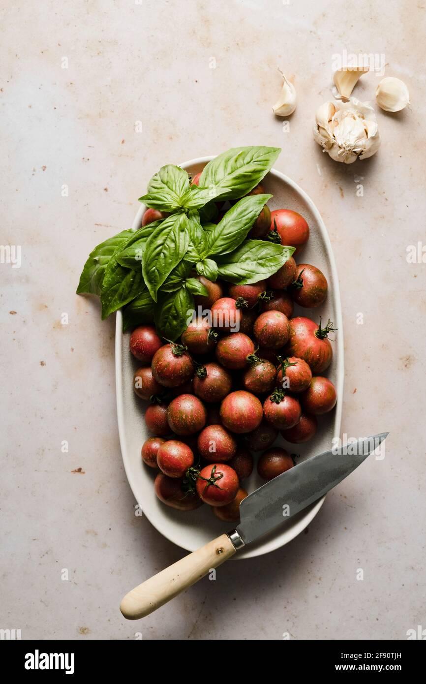 Ganze und in Scheiben geschnittene Kirschtomaten in einer Schüssel mit Basilikum- und Knoblauchzehen. Stockfoto