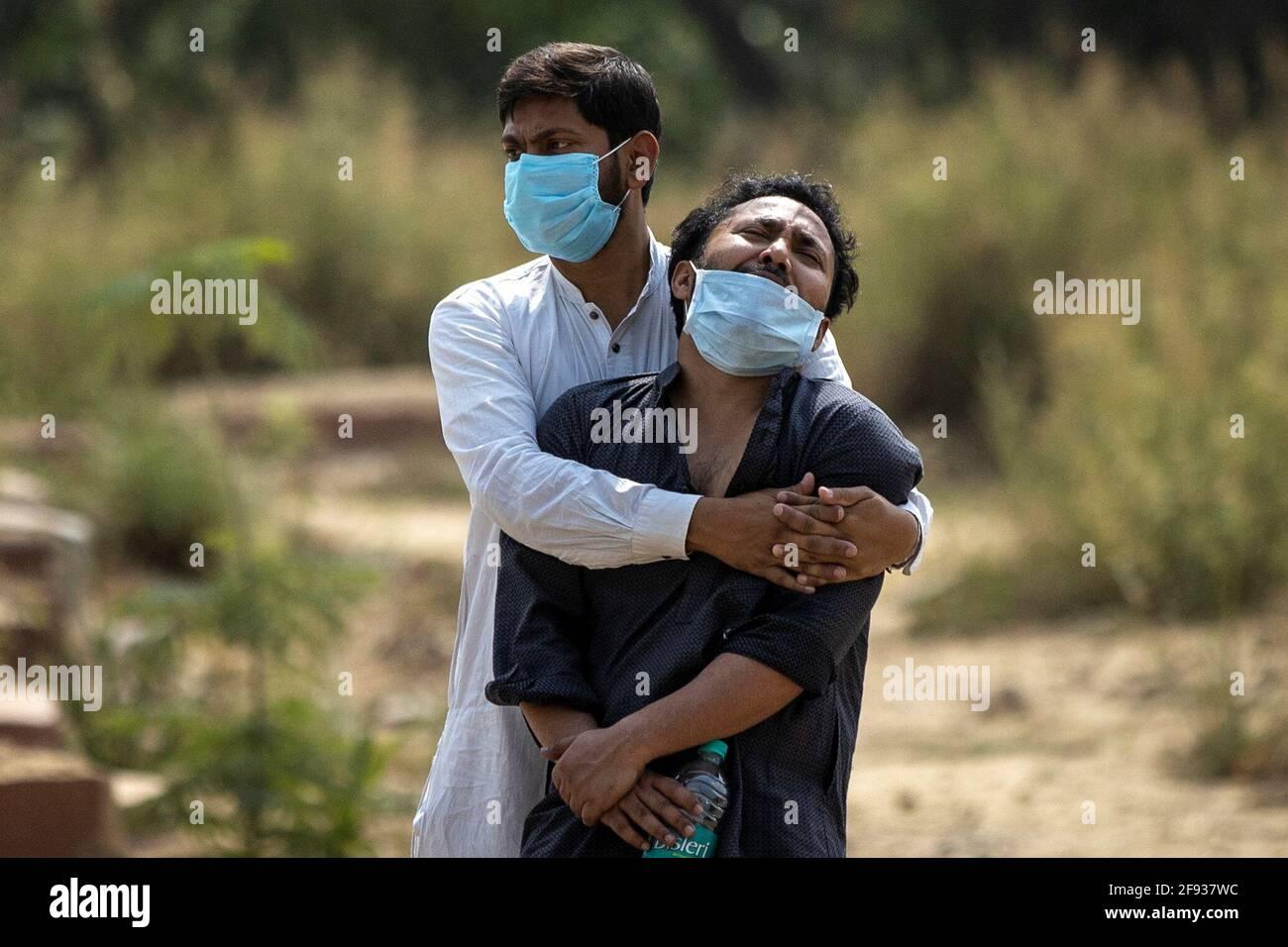 Ein Mann wird von seinem Verwandten getröstet, als er den Leichnam seines Vaters sieht, der an der Coronavirus-Krankheit (COVID-19) starb, bevor er am 16. April 2021 auf einem Friedhof in Neu-Delhi, Indien, begraben wurde. REUTERS/Danish Siddiqui Stockfoto