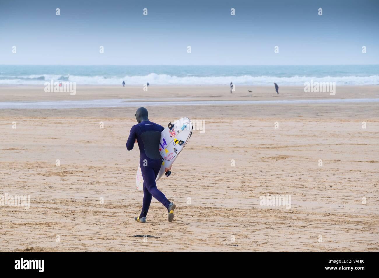 Ein Surfer mit seinem Surfbrett und läuft über Crantock Beach in Newquay in Cornwall. Stockfoto