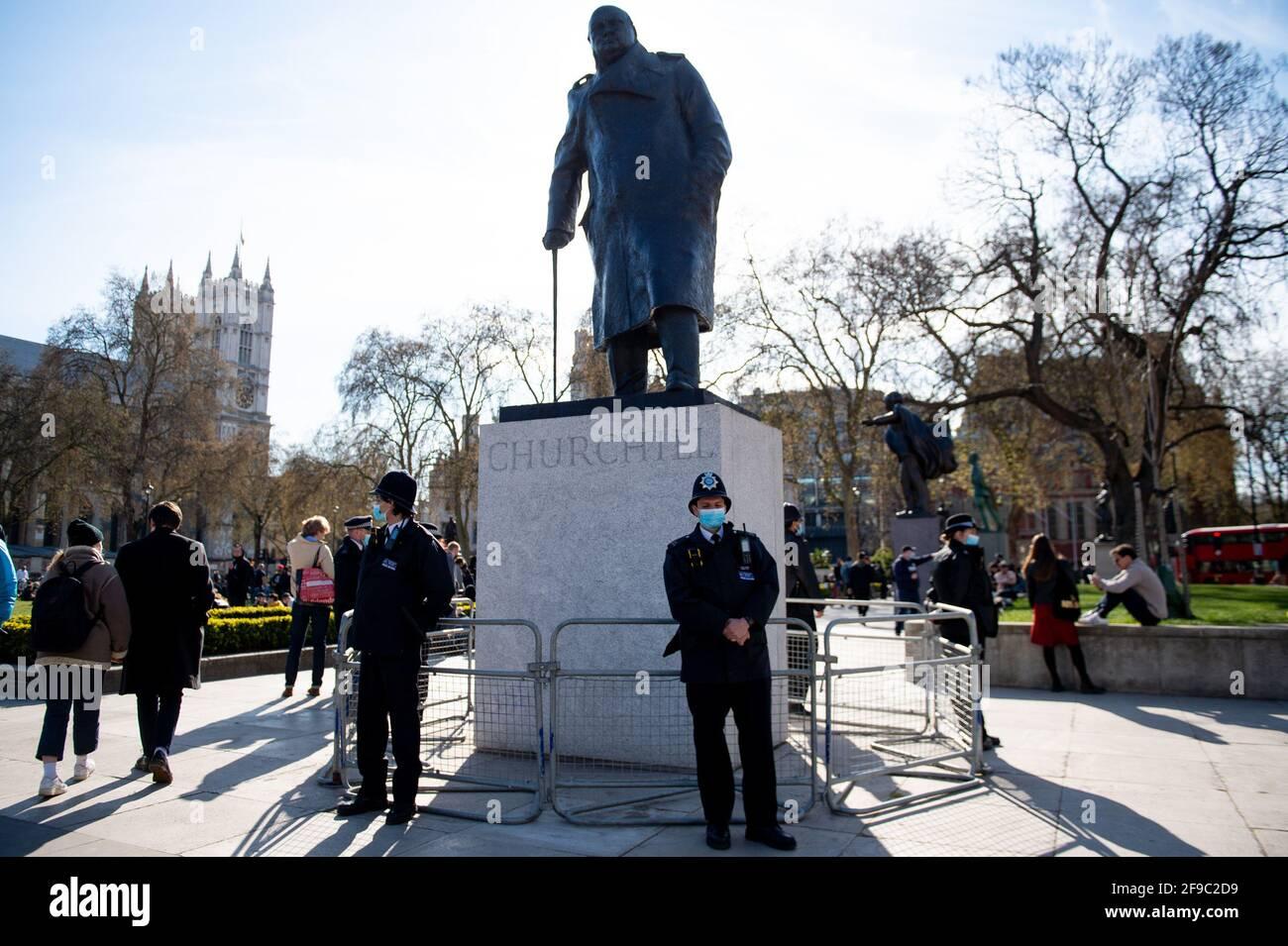 """Polizeibeamte stehen bei einer Statue von Winston Churchill während eines Protestes """"Kill the Bill"""" gegen das Gesetz über Polizei, Verbrechen, Verurteilung und Gerichte auf dem Parliament Square in London. Bilddatum: Samstag, 17. April 2021. Stockfoto"""