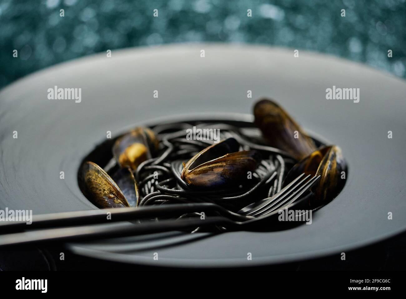 Schwarze Spaghetti mit Meeresfrüchten und Venusmuscheln auf schwarzem Teller Auf dunklem Stein Stockfoto
