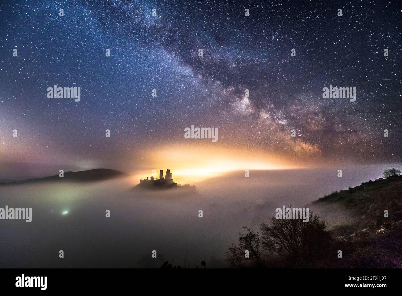 Corfe Castle, Dorset, Großbritannien. April 2021. Wetter in Großbritannien. Die Milchstraße leuchtet hell über dem Schloss Corfe in Dorset, das in einer kalten, klaren Nacht von einem dichten Nebelmeer umgeben ist. Bildnachweis: Graham Hunt/Alamy Live News Stockfoto