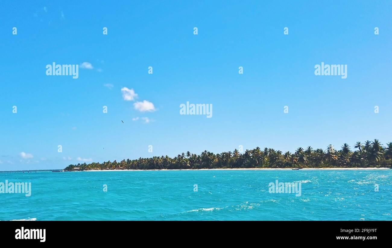 Türkisfarbenes, tropisches Meerwasser und blauer Himmel. Strand mit Palmen am Horizont. Exotischer Urlaub in der Dominikanischen Republik. Stockfoto
