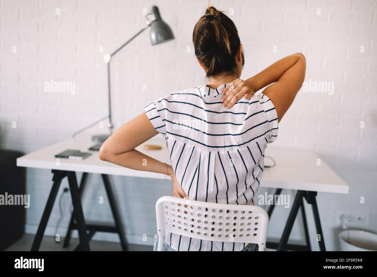 Überforderten Frau mit Rückenschmerzen im Büro mit schlechter Haltung Stockfoto